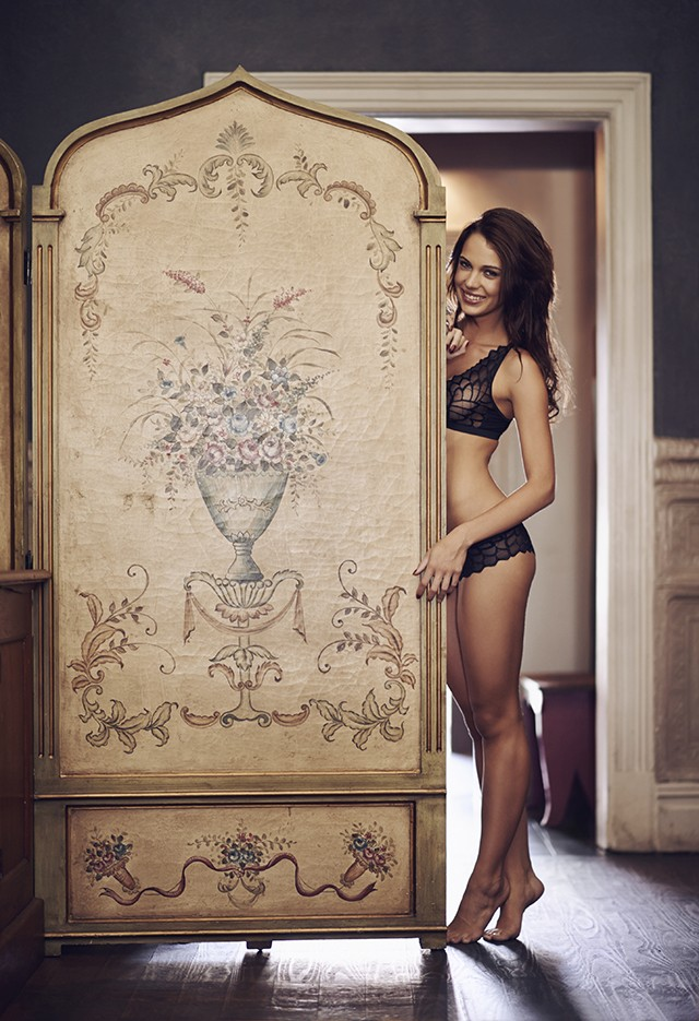 A young woman seductively posing behind a room devider in lingerie