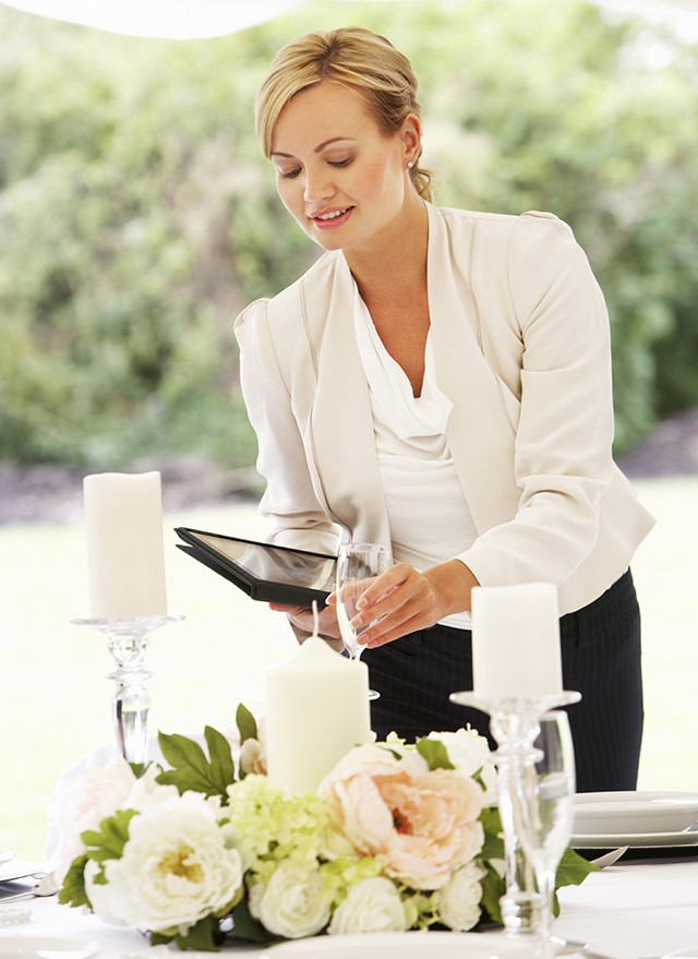 Wedding Planner Checking Table Decorations In Marquee