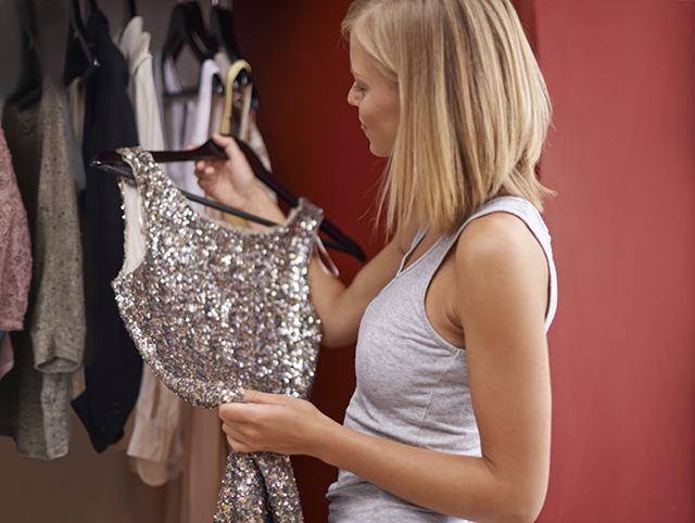 A young woman picking out a dress from her closet
