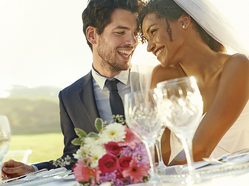 Shot of a happy bride and groom sitting at a table