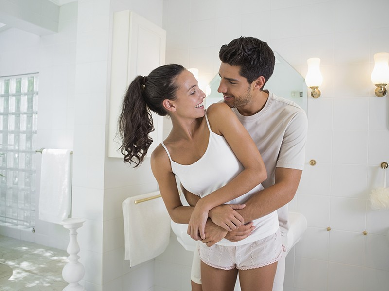 Smiling couple embrace and look at each other at home in bathroom