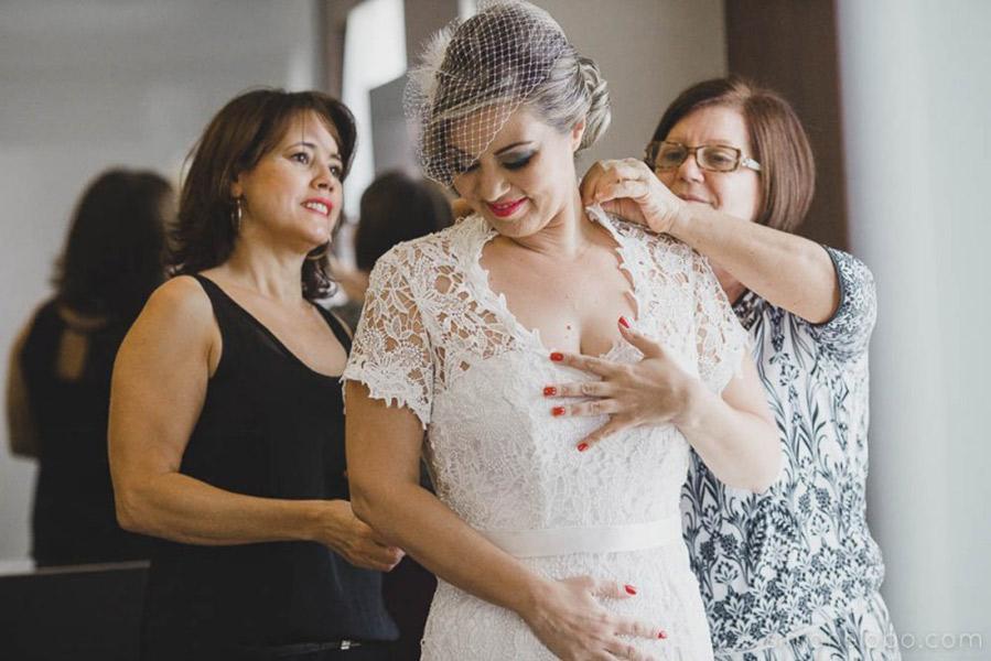 Mãe da noiva arrumando ela para o casamento.