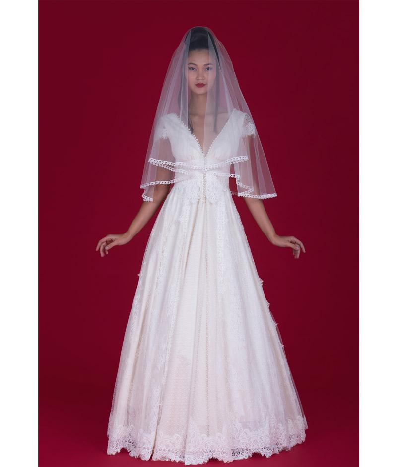Noiva com vestido de renda e véu sobre o rosto pó de arroz
