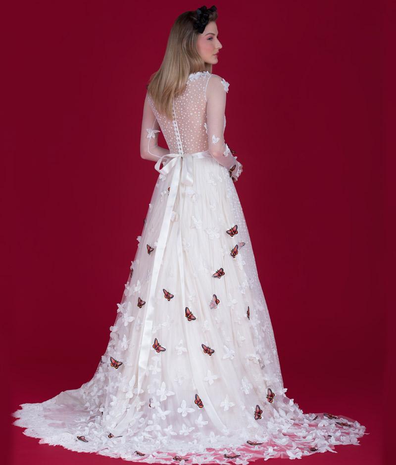 Noiva de costas com vestido com transparência laço na cintura e borboletas em relevo da pó de arroz