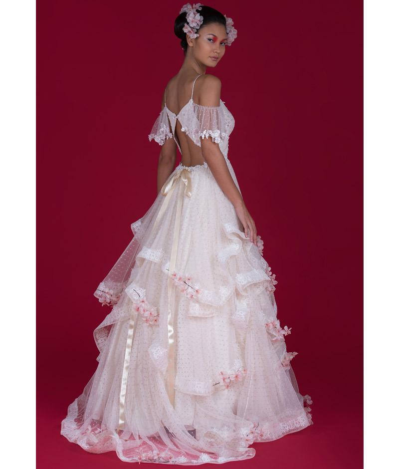 Noiva de costas com vestido de transparência e flor de cerejeira em relevo pó de arroz