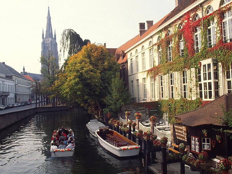 Turistas passeando no canal de Bruges