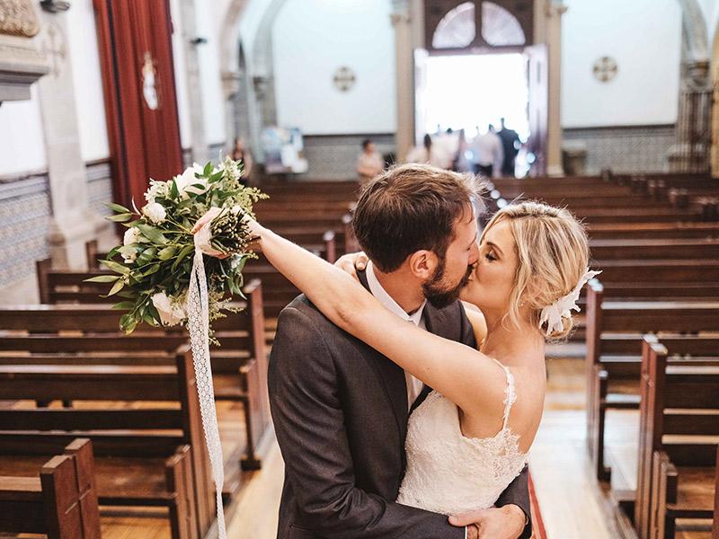 Casamento em Portugal final da cerimônia noivos se beijando na igreja