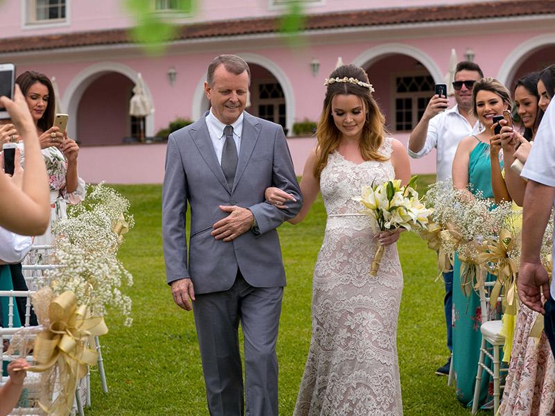 Casamento ao ar livre noiva caminhando até o altar com o pai