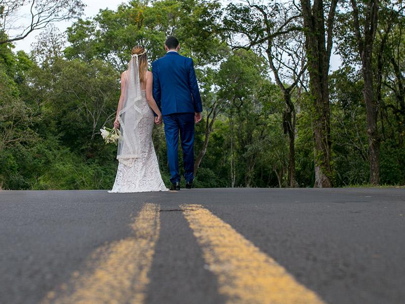 Casamento ao ar livre noivos de costas para câmera em uma estrada