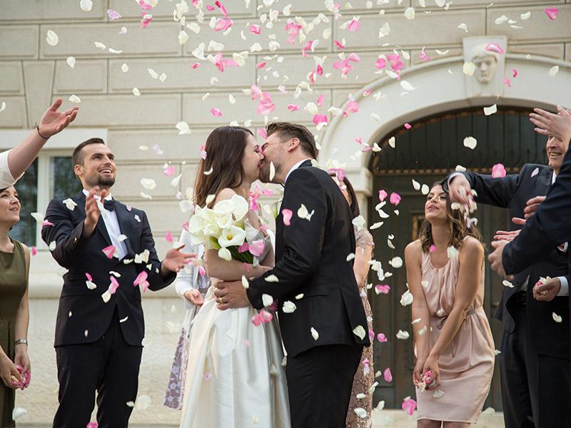 Organização de casamento noivos se beijando na saída da cerimônia com chuva de pétalas de rosas