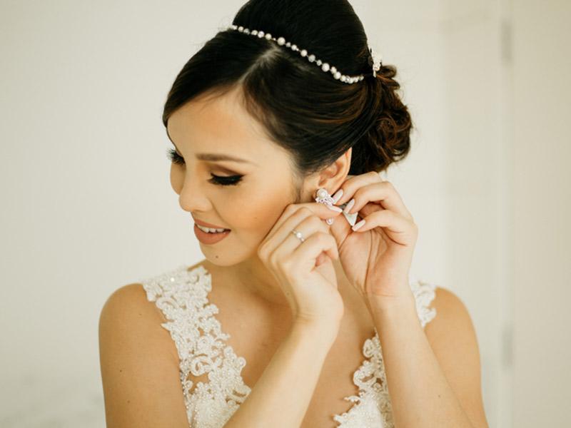 Unha da noiva colocando brinco com esmalte branco bem delicado