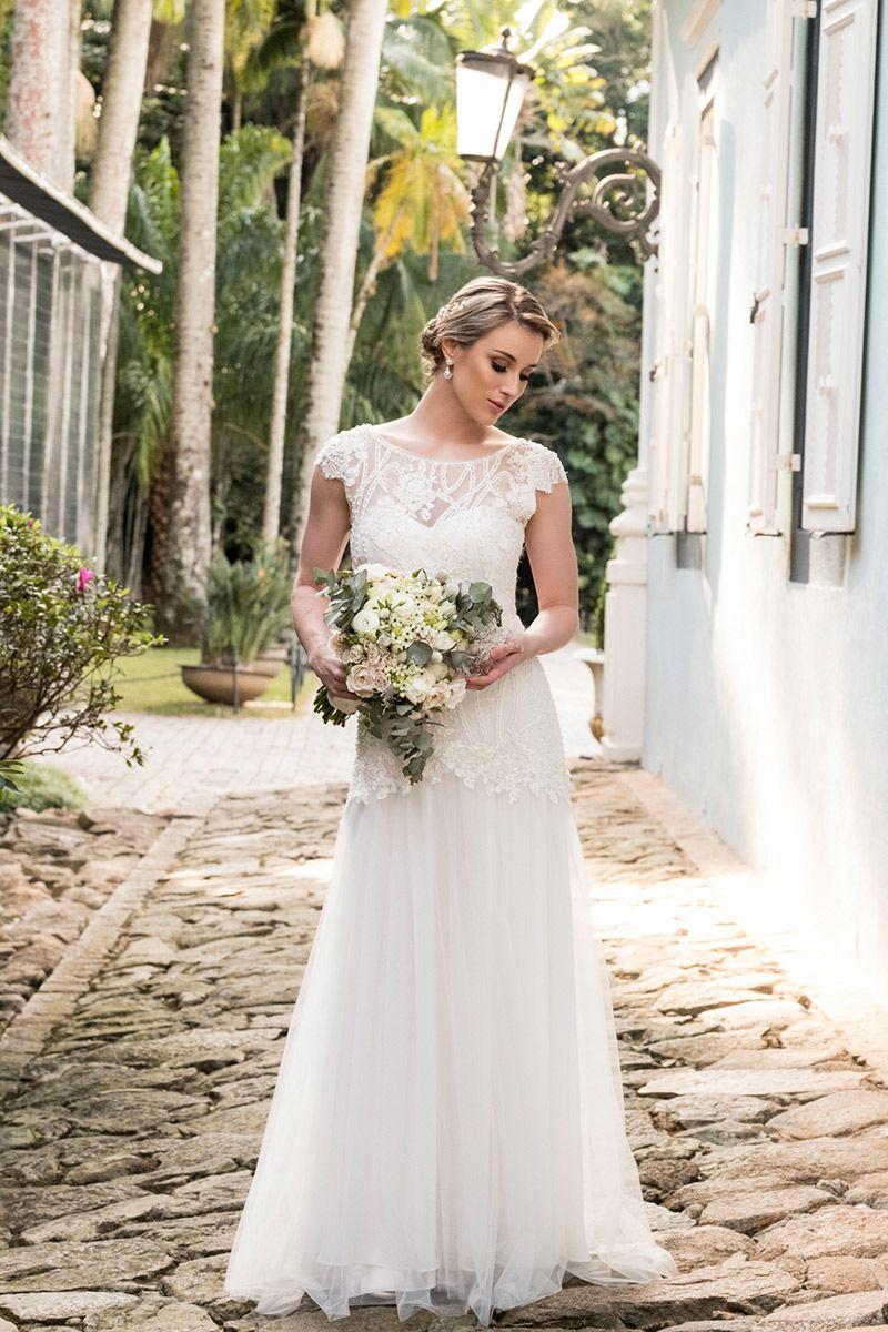 Vestido de noiva com transparência e renda modelo com buquê