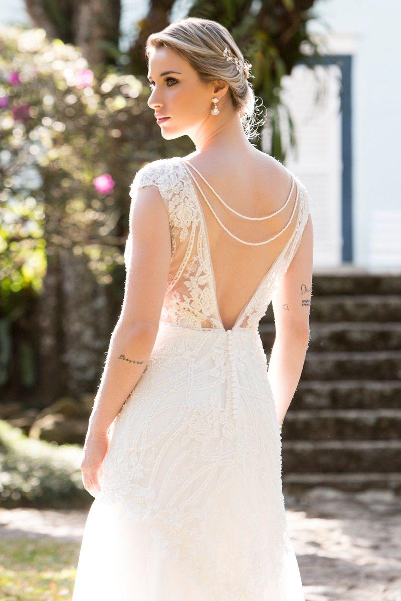Vestido de noiva modelo de costas mostrando decote v com cordões de pérolas
