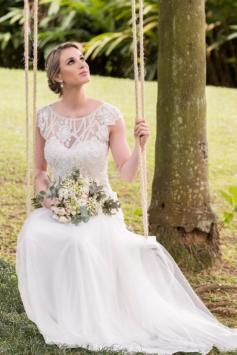 Vestido de noiva para casamento no campo modelo sentada no balanço com vestido com transparência renda e mangas