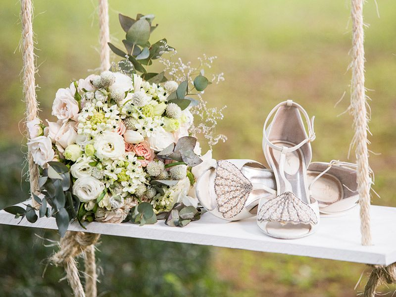 Vestido de noiva par de sapatos no balanço com buquê ao lado