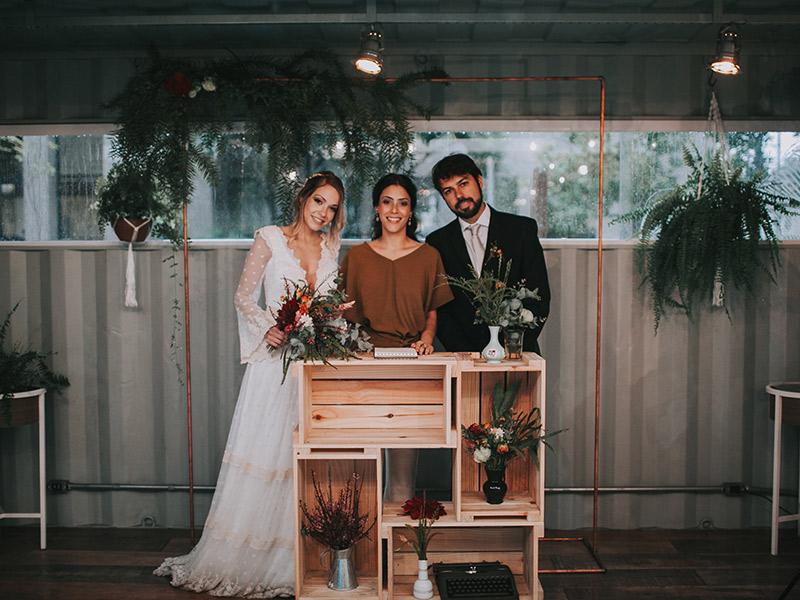 Casamento boho chic noivos posando com cerimonialista