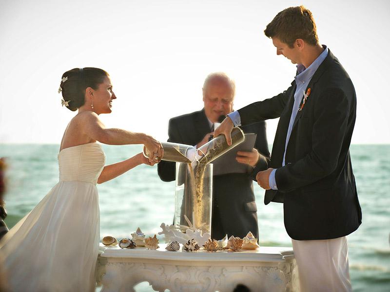 Cerimônia de casamento noivos celebrando com areia