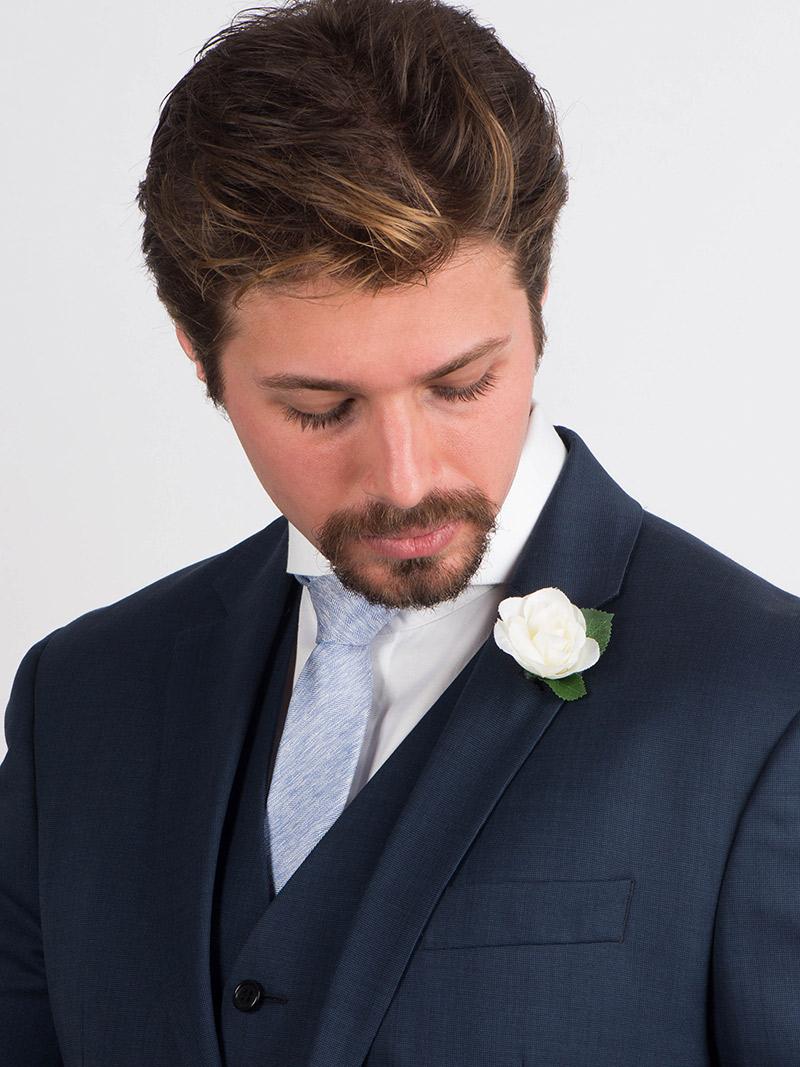 Flor de lapela camélia e noivo com terno azul