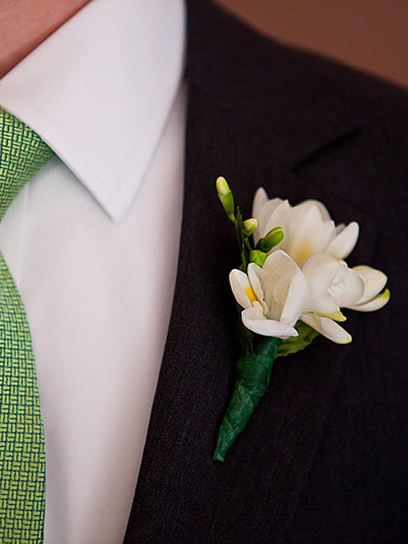 Flor de lapela jasmin e noivo com terno preto