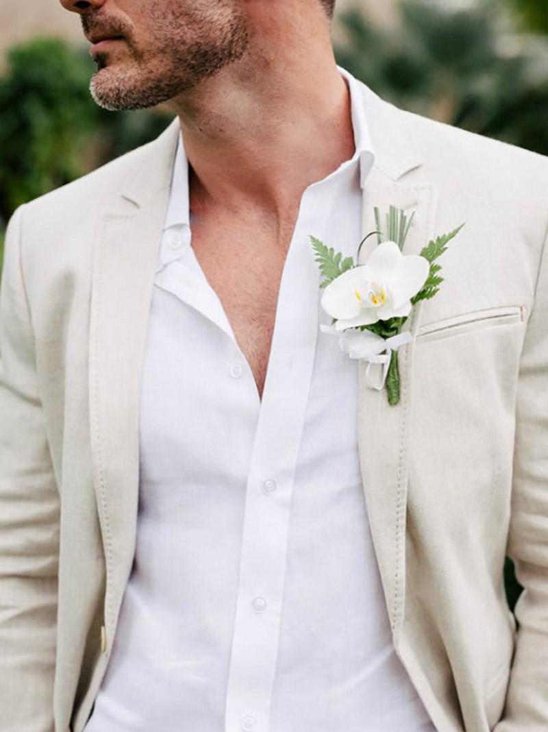 Flor de lapela orquídea branca e noivo com terno bege