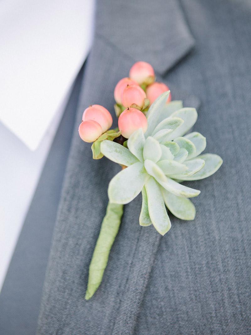Flor de lapela suculenta e noivo com terno cinza