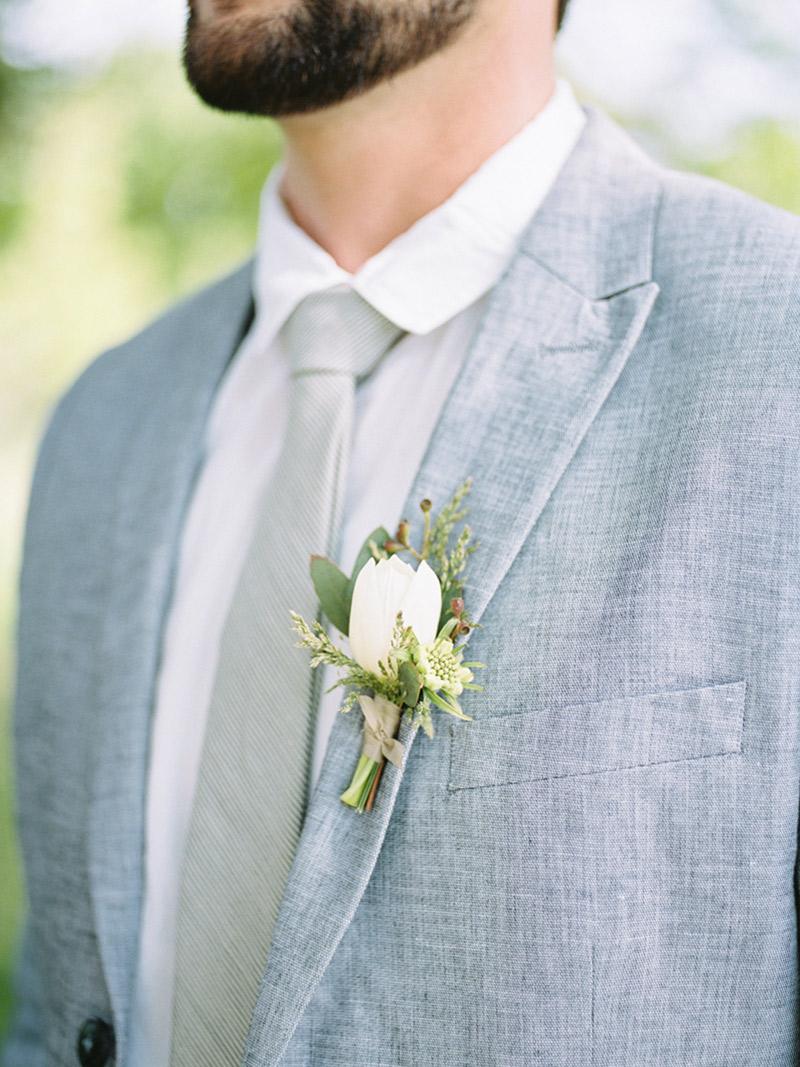 Flor de lapela tulipa e noivo com terno cinza claro
