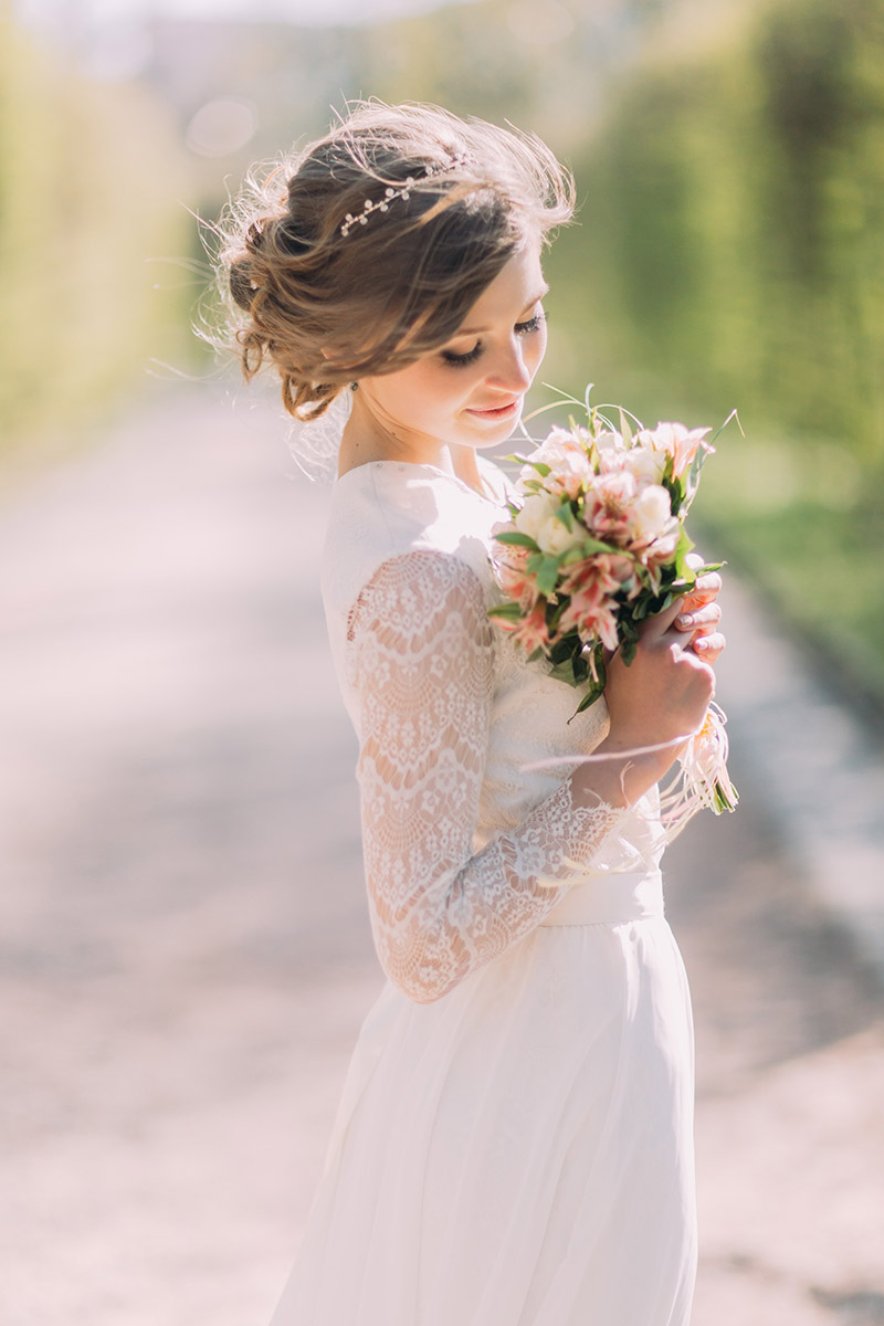 Beautiful blonde bride with bouquet of spring flowers outdoor