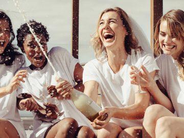 Noivas estourando champanhe durante brincadeiras para chá de cozinha