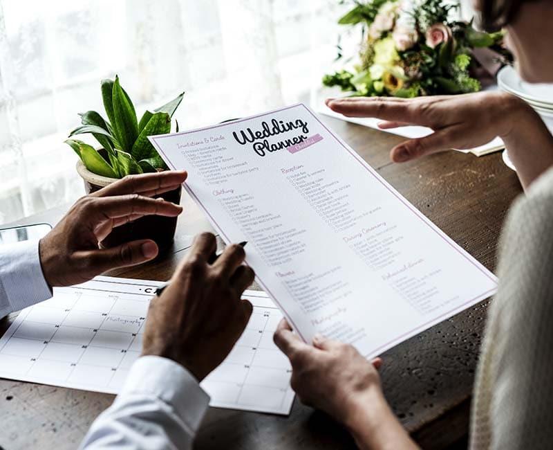 mãos segurando um planner de casamento