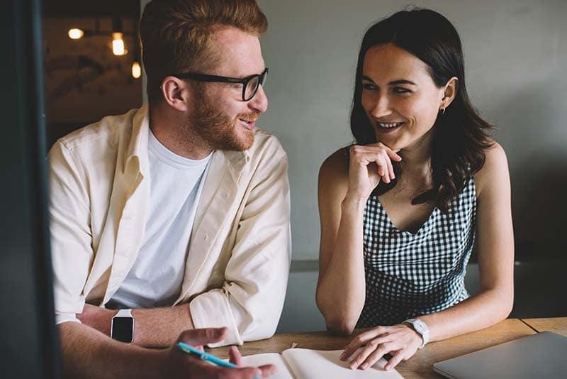 Um casal de homem e mulher usando um notebook que está em cima de uma mesa aberto. O homem está segurando uma caneta e explicando algo para mulher que está sorrindo