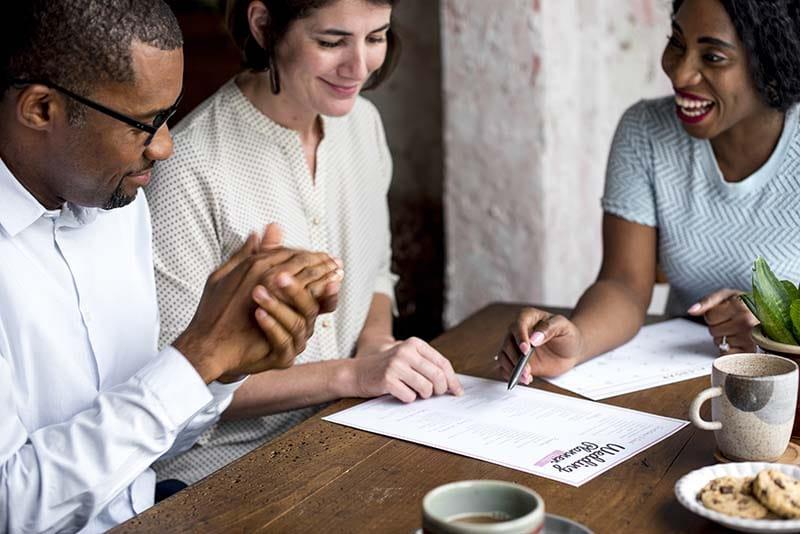 casal de homem e mulher conversando com outra mulher e olhando um planner de casamento