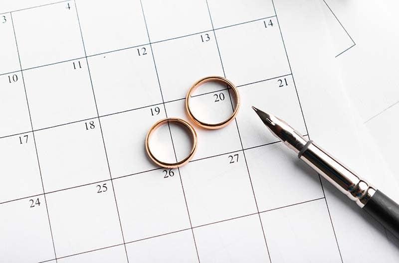 alianças de casamento douradas em cima de um calendário simbolizando a data do casamento