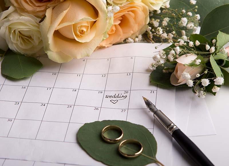 duas alianças douradas, em cima de um calendário com flores em volta