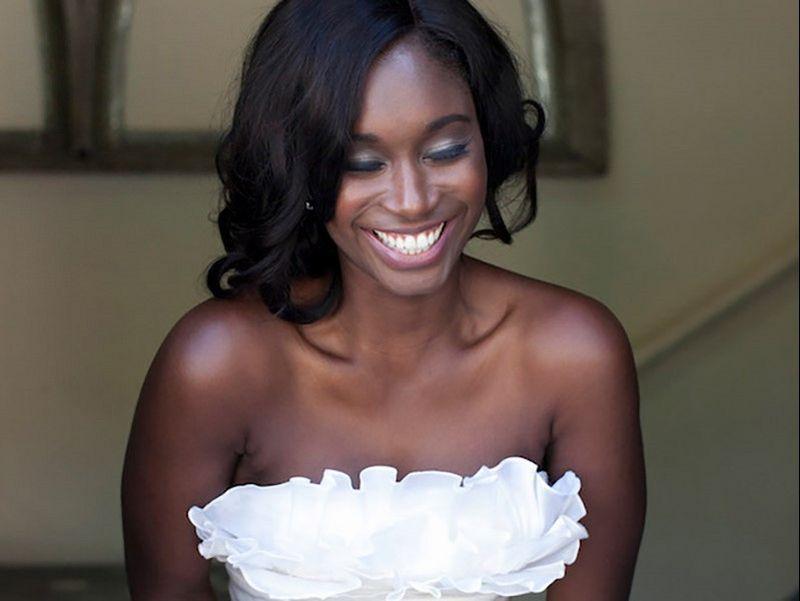 Noiva de olhos fechados e rindo no dia do casamento