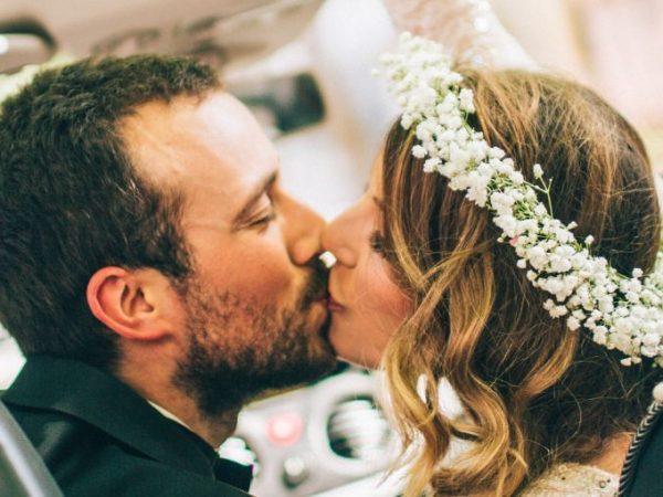 Casal se beijando no carro após casamento