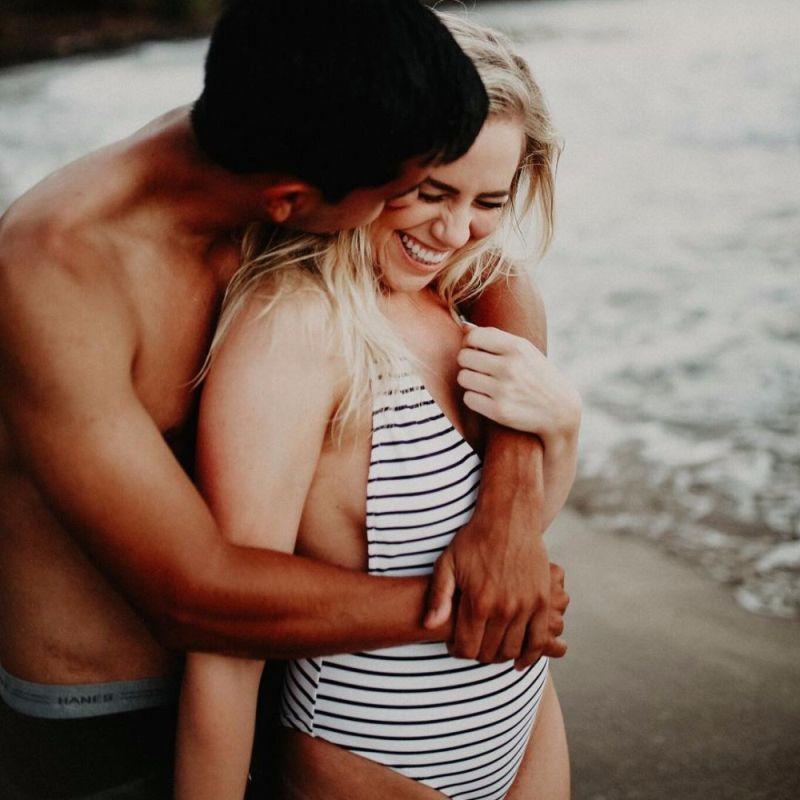 Casal se abraça na praia