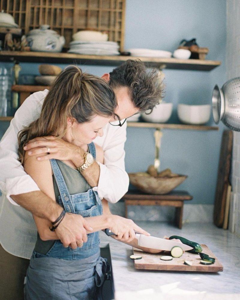 Casal se abraçando enquanto cozinham juntos