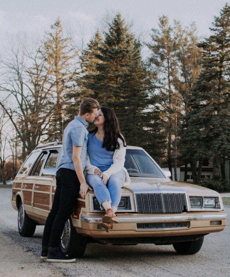 Casal se beija enquanto estão encostados no carro