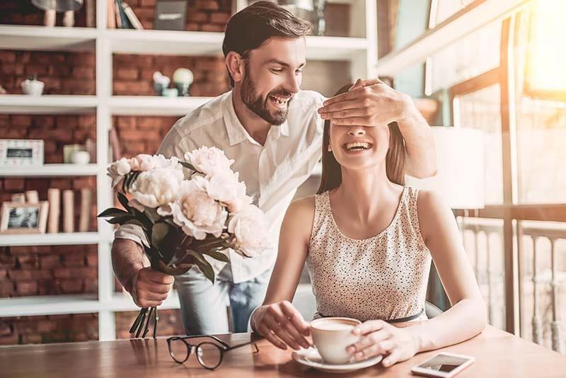 Bodas de casamento de um homem segurando um buquê de flores brancas, enquanto ele tampa o olho da mulher, que está sorrindo e tomando café