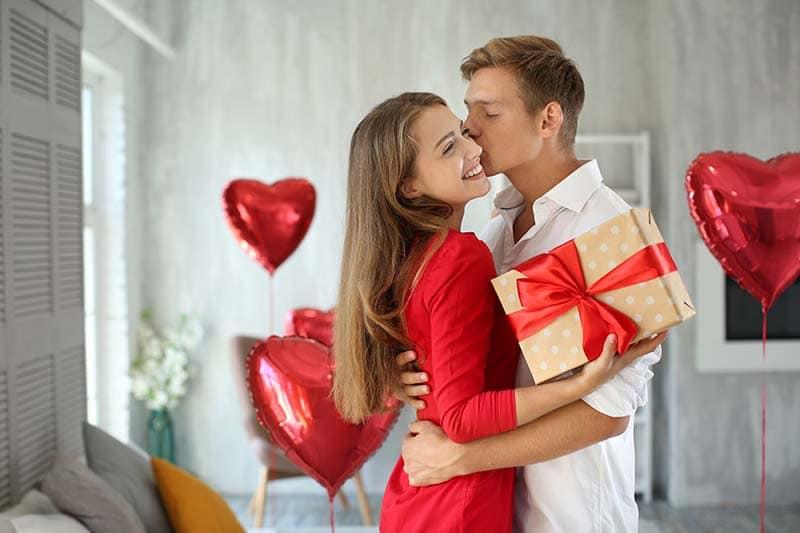 Bodas de casamento de um casal se beijando. A mulher está segurando um embrulho de presente.