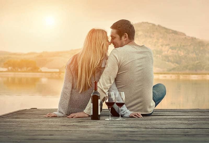 Bodas de casamento de um casal sentado em um pier tomando uma taça de vinho tinto