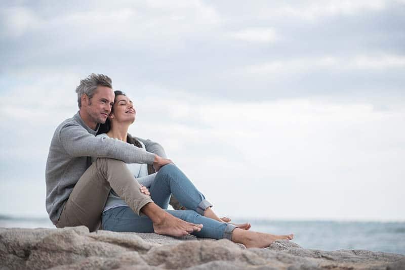 Bodas de casamento de casal de meia idade se abraçando na praia