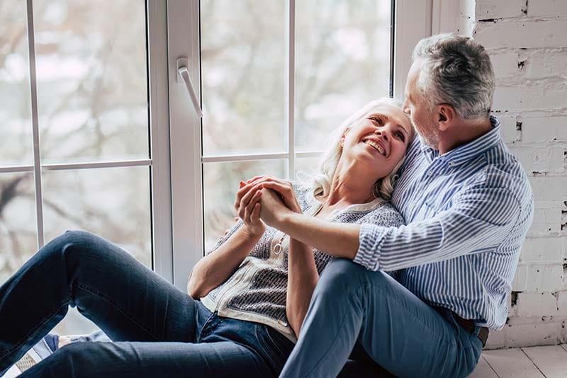 Bodas de casamento, casal se olhando e se abraçando na janela