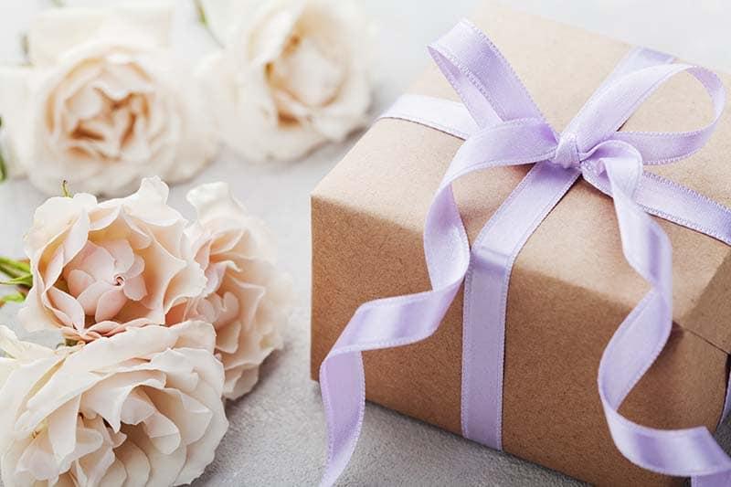 Presente de casamento embrulhado com uma fita lilás e rosas ao lado compondo a imagem