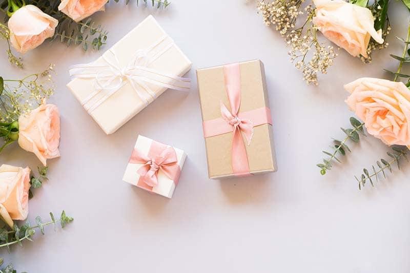 Foto de presentes de casamentos pequenos embrulhados com rosas ao lado