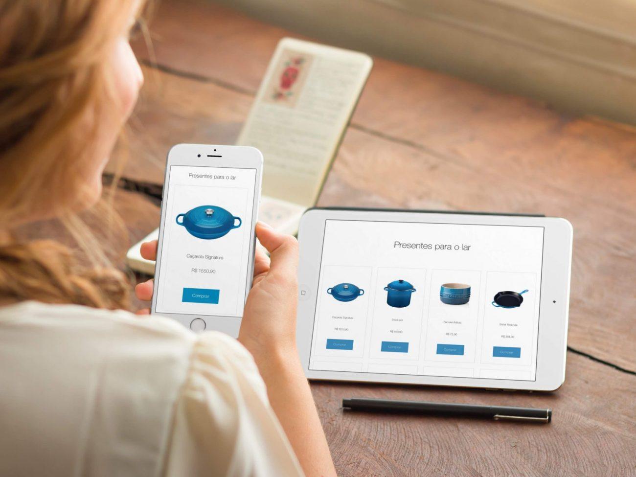 uma mulher segura um celular onde mostra uma lista de presentes de casamento virtual, e na frente dela também aparece uma lista em um tablet, com produtos para o lar, como panelas