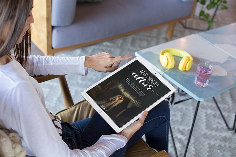 Na imagem vemos uma mulher segurando um iPad onde é possível ver a capa do E-book 12 passos ao altar como ajuda para o check list de casamento