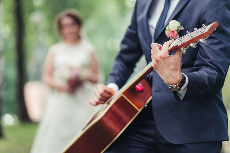 Na imagem aparece um homem tocando violão e ao fundo uma mulher vestida de noiva. Música para casamento 2021
