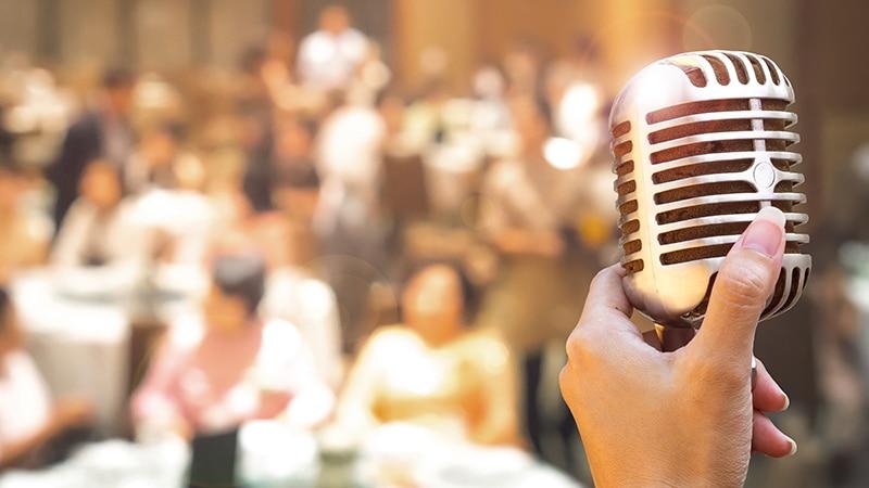 imagem mostra com fundo distorcido um casamento e em destaque um microfone antigo. Música para casamento 2021