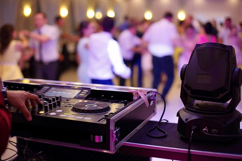 imagem mostra uma mesa de dj e ao fundo pessoas dançando durante uma festa de casamento. Música para casamento 2021